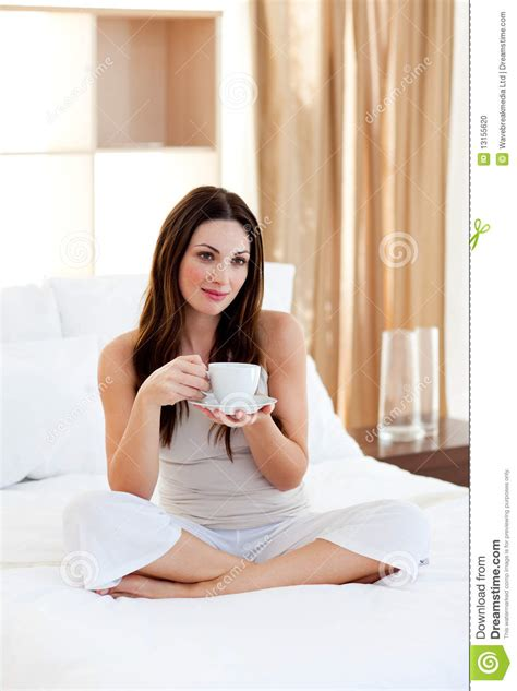 Beautiful Home Interiors Pictures by Attractive Woman Drinking Coffee Sitting On Bed Stock