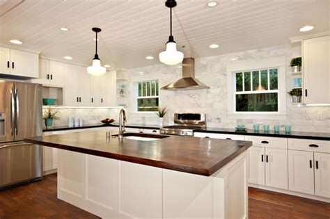 white kitchen island with black granite top white kitchen with wood island carrara backsplash black