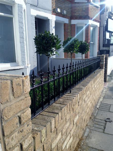 garden wall metal yellow brick garden wall metal rail and gate bay and buxus