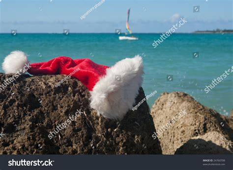 rock the boat a hat in time santa hat on a rock with a holiday sea in the background