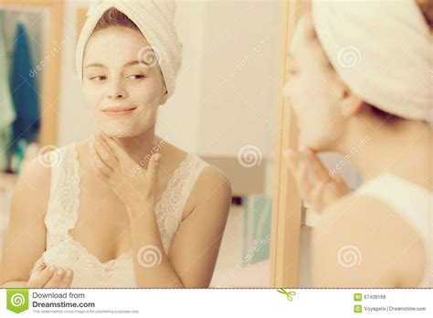 bathroom facial woman applying mask cream on face in bathroom stock photo