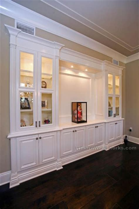 classic wall units living room lighted with simple trim and classic effects like the glassed enclosure to keep books clean