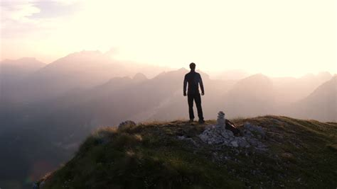 man standing on mountain top aerial flying around young man standing victoriously on