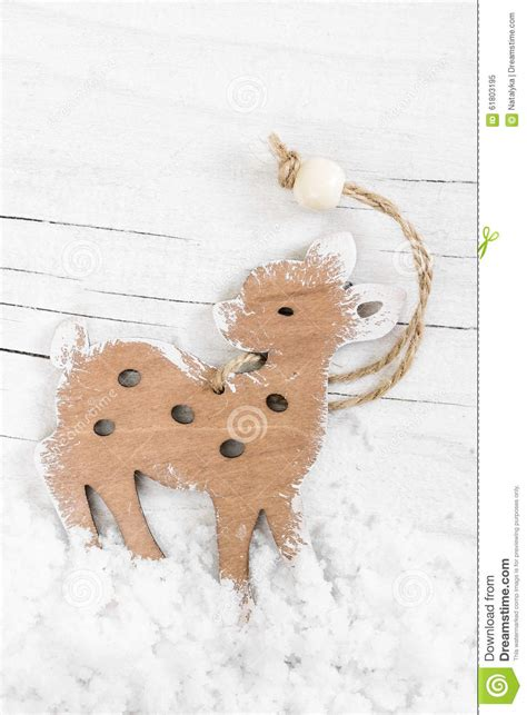 decorative wooden small deer on the snow wooden background