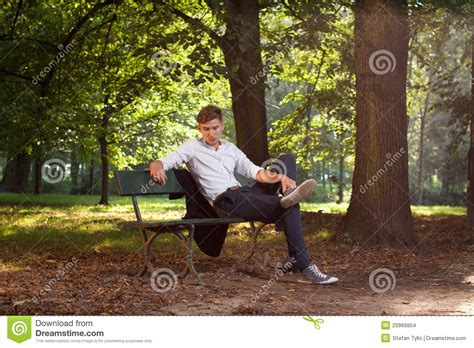 sit on a bench male model sitting on a bench stock images image 20966854