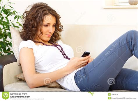 girl on couch girl on a couch using a mobile phone royalty free stock