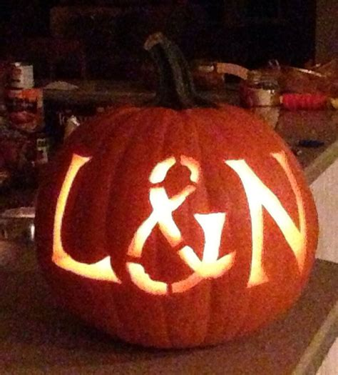 initials of the engaged couple carved in a pumpkin for their fall engagement party everyone