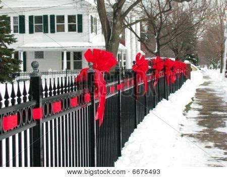 ideas for decorating iron fence posts for christmas ribbon bows on the iron fence along a small town time