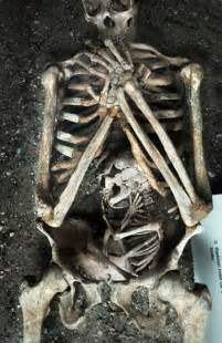 a skeleton of a mother and her baby who both died during