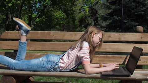 girls bench a teenager with a laptop in the park on a bench a girl in