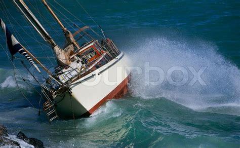 crash boat weather yacht crash on the rocks in stirmy weather stock photo