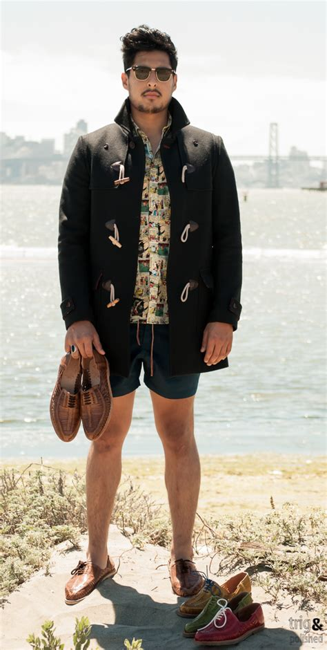 s black duffle coat yellow print sleeve shirt teal shorts brown woven leather