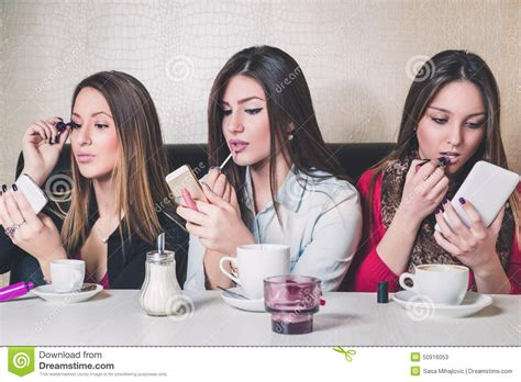 portrait of teenage girl putting lipstick on while looking at her three girls putting on makeup in a cafe stock photo
