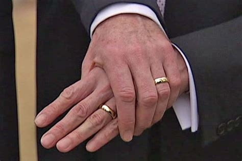 two men wearing wedding bands holding hands abc news
