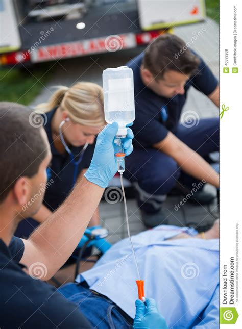 can i drink water before c section paramedic team preparing drip for injured patient stock
