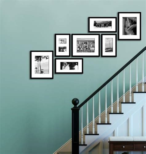 how to hang family photos on the wall family photos display along the staircase on the blue wall