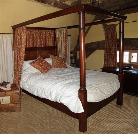 18th century style oak 4 poster bed in heavily beamed room