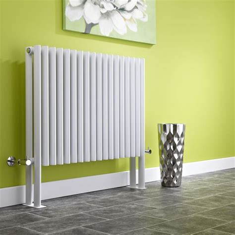 we love this grey radiator against the green background we love the contrast of this white designer radiator