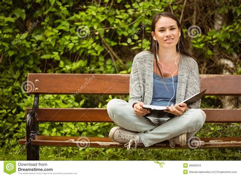 sitting on a park bench song smiling student sitting on bench listening music with