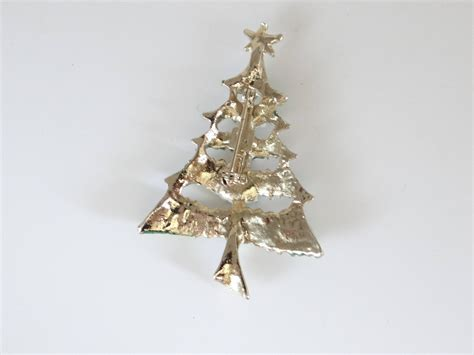 gold tipped christmas tree vintage tree brooch with rhinestone and green snow tipped branches on a gold