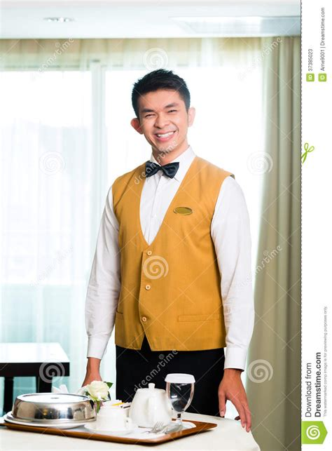 asian room service waiter serving food in hotel