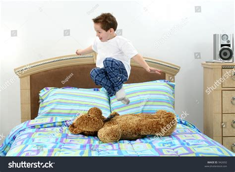 5 year old bed five year old boy in pajamas jumping in bed stock photo
