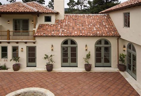 exterior of a style luxury home with stucco walls a tile roof and mexican tile patio