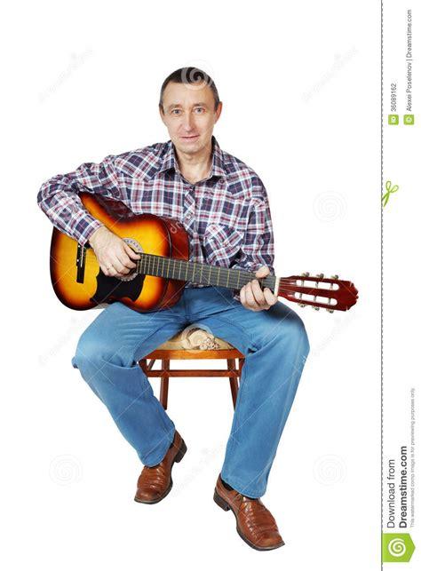 stuhl zum gitarre spielen bemannen sie spiele eine gitarre die auf einem stuhl