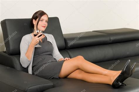 Sit On Sofa by Businesswoman Sit Leather Sofa Drink Wine Stock