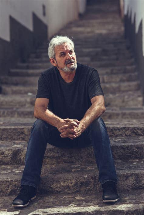 homem maduro sentado em degraus em fundo urbano baixar