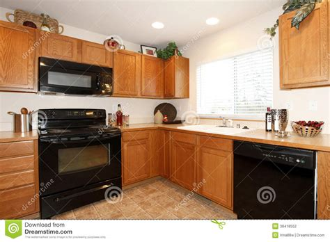 brown kitchen cabinets with black appliances stock