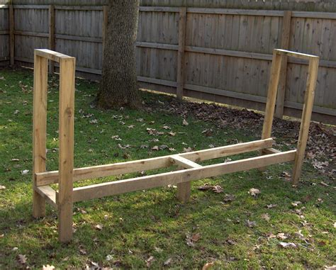 build a firewood rack the easy way simple diy outdoor firewood rack in the backyard with green grass garden and wooden fence ideas