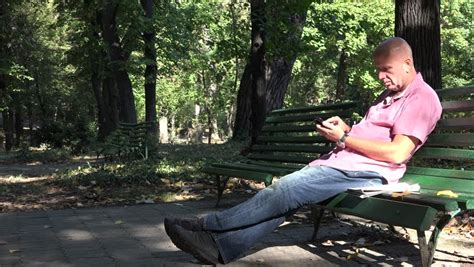 sitting on a park bench song men sitting on park bench and make a phone call stock