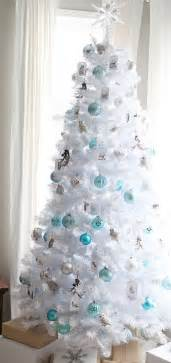 Crispy white christmas tree decorated in blue and silver breathes with