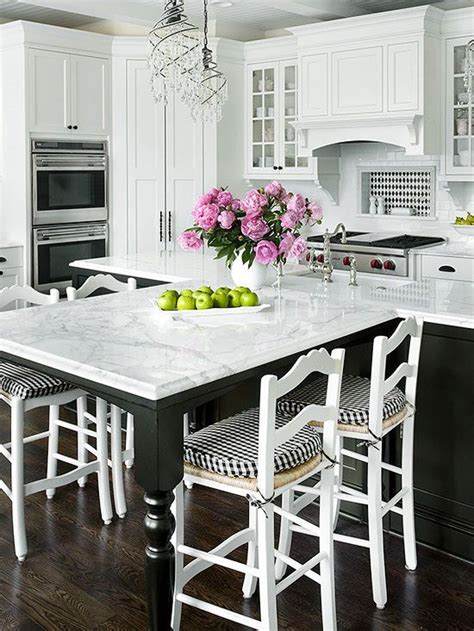 white kitchen island with seating extended seating off the island and the black white