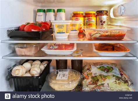 Refrigerated Chicken Shelf by Cooled Food In Open Fridge Refrigerator In Kitchen Stock
