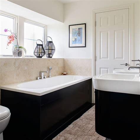cream bathroom with black bath and basin housing
