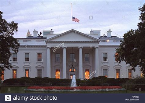 white house flag american flag flies at half staff over the white house at sunrise stock photo royalty