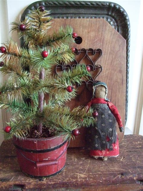 old red bucket stuffed with a feather tree christmas