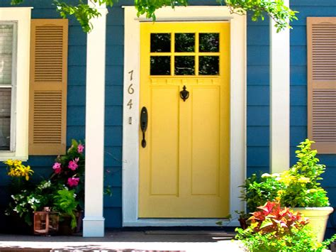 bright blue house wall painting paired with yellow front door color between windows plus