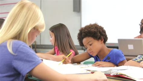 Teacher Sitting At Desk Next To Female Student As They Student Working At Desk