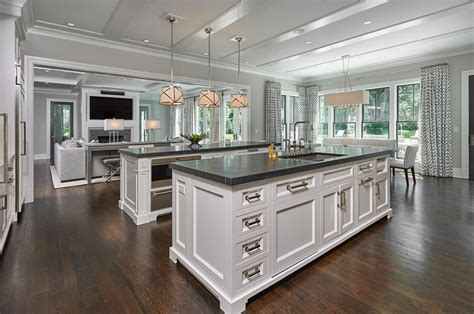 side by side white kitchen islands with honed black marble