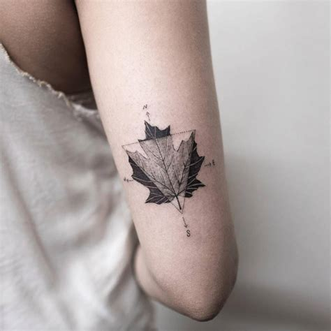 maple leaf and compass tattoo on the back of the right arm