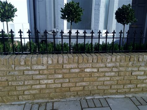 metal wall for gardens yellow brick garden wall metal rail and gate bay and buxus