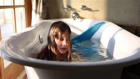 mermaid bathtub 9 year old girl with fake mermaid costume in bathtub stock