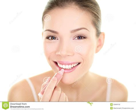portrait of teenage girl putting lipstick on while looking at her lipstick makeup woman putting lip balm care beauty stock