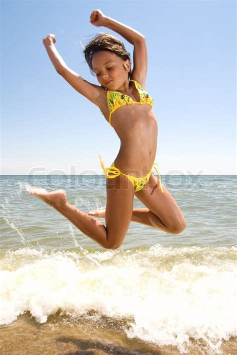 young little girl models spread little girl jumping at the seaside stock photo colourbox
