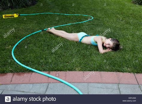 8 years in years 8 year lying on lawn in swimsuit with sprinkler stock photo royalty free