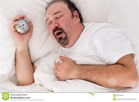 lying in bed all day lethargic man yawning as he struggles to wake up stock