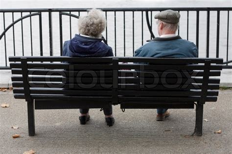 two people sitting on a bench two elderly people sitting on a bench stock photo